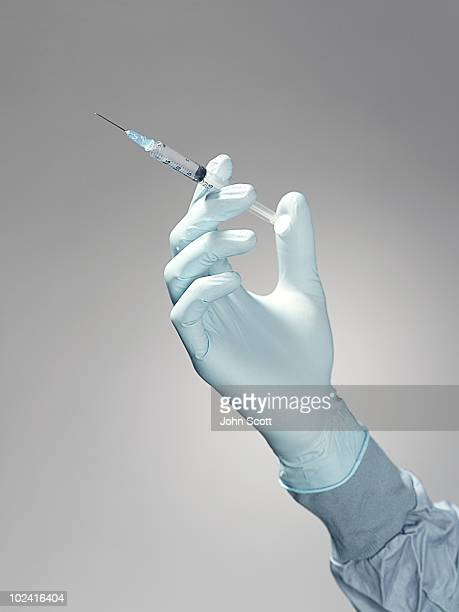 hand holding a syringe  - surgical equipment stock photos and pictures