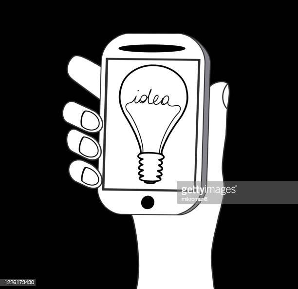 hand holding a telephone with light bulb with the word idea - black and white stock pictures, royalty-free photos & images