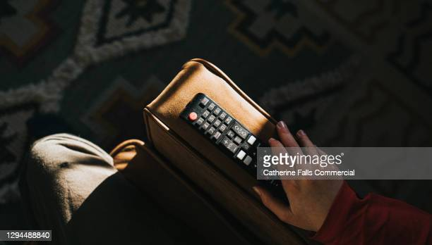 a hand holding a television remote control on the arm of a sofa - publicity event stock pictures, royalty-free photos & images