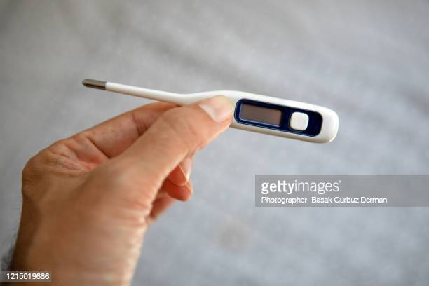a hand holding a thermometer - cold and flu stock pictures, royalty-free photos & images