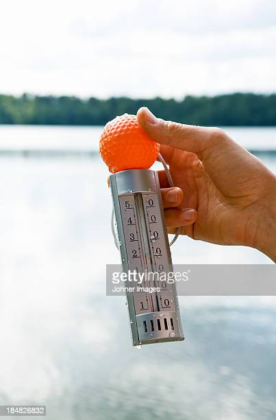 a hand holding a thermometer, sweden. - dalsland stock photos and pictures