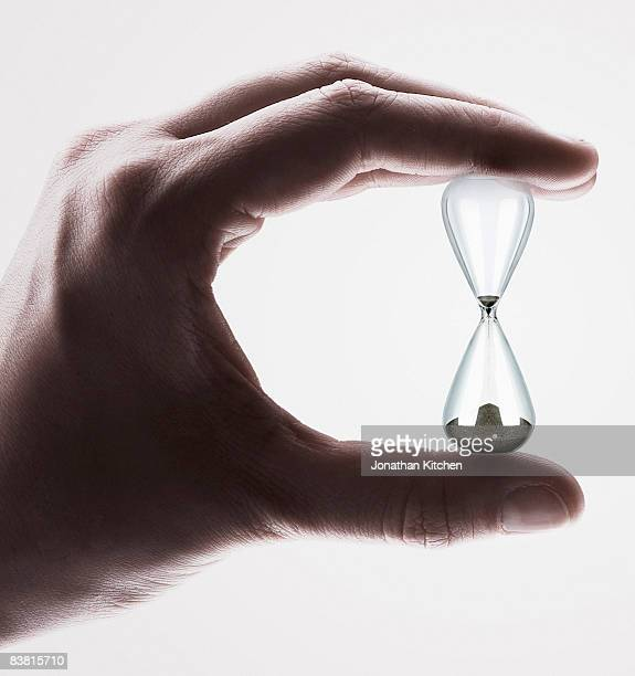 Hand Holding a traditional egg timer Hourglass