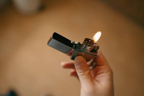 Hand holding a vintage metal windproof lighter