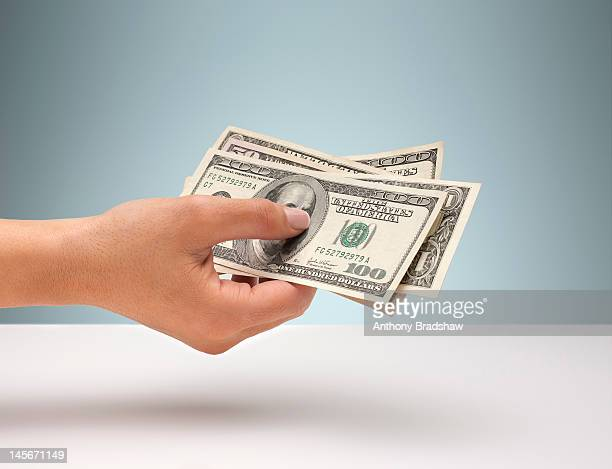 hand holding american currency - us dollar note stock photos and pictures