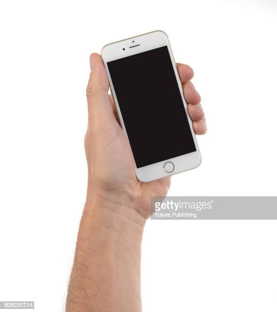 A hand holding an Apple iPhone 6 smartphone with a Gold finish taken on April 29 2015