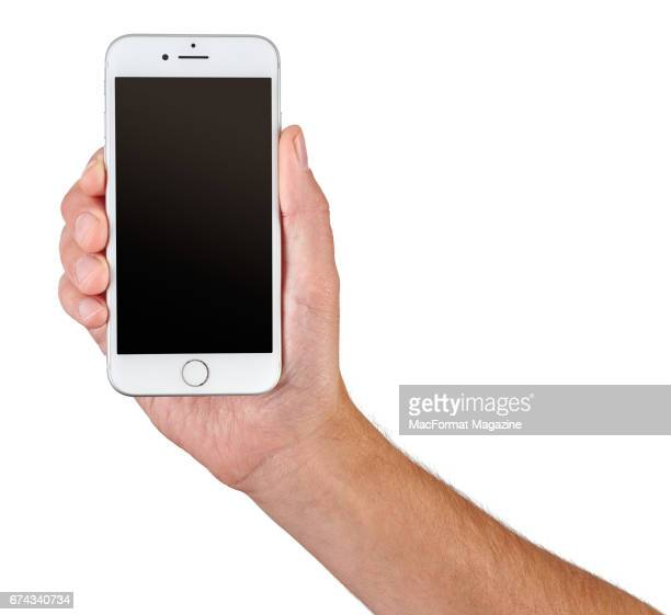 A hand holding an Apple iPhone 7 with a Silver finish taken on September 23 2016