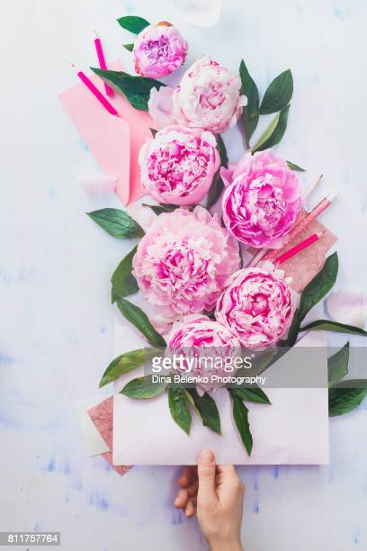 Hand holding an envelope full of pink flowers with pencils and notes on a light background