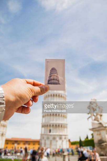 Hand holding an instant photo against the Leaning Tower of Pisa