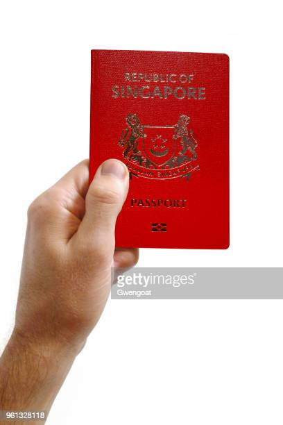 Hand holding an Singaporean passport against a white background