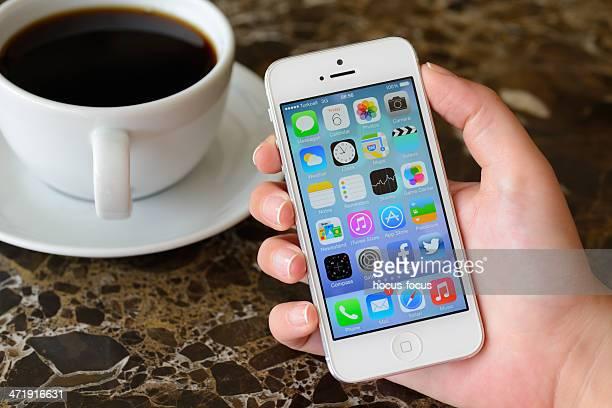 Main tenant l'Apple iPhone 5 écran d'accueil affichage