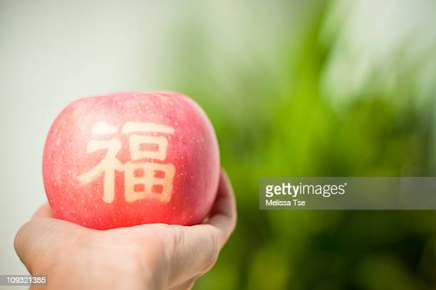 Hand holding apple with chinese character on it