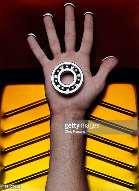 Hand holding ball bearings in oil