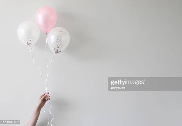 hand holding balloons with confetti inside