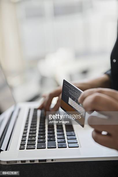 Hand holding bank card while using laptop