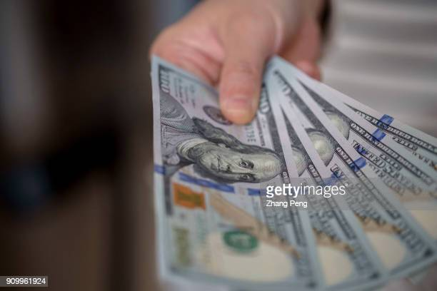 Hand holding banknotes of US Dollar, arranged for photography. Recently, the exchange rate of RMB vs US Dollar has continued to rise sharply. The...