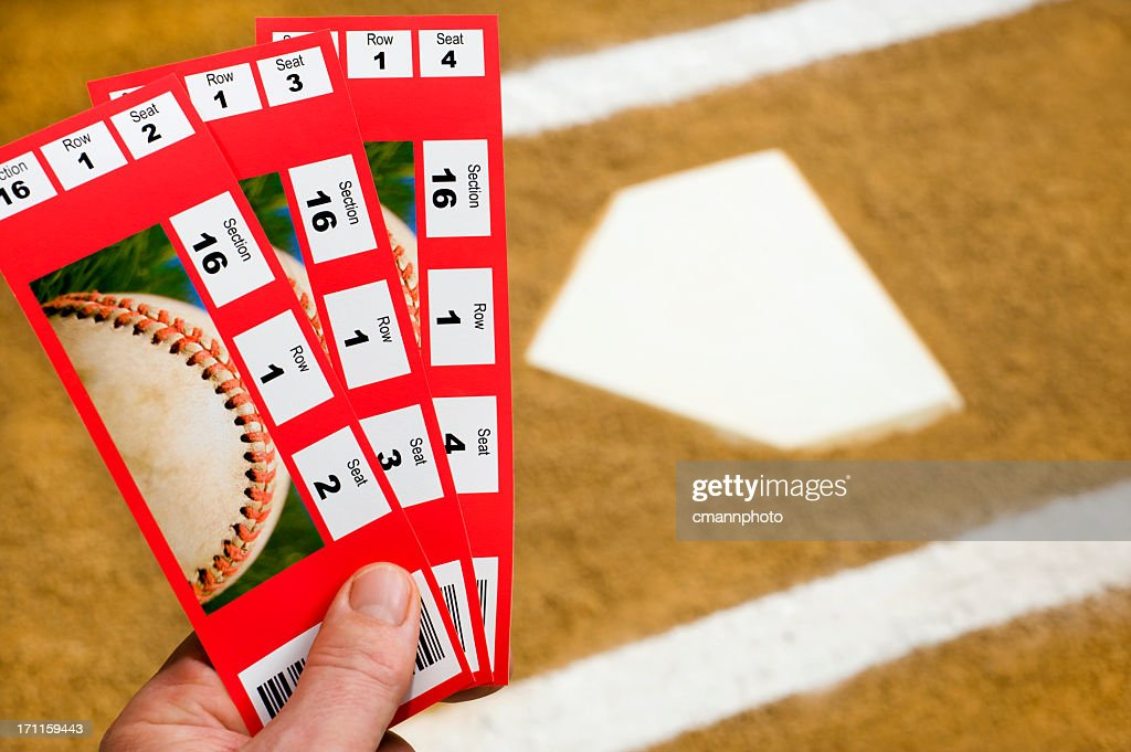 Hand holding Baseball Tickets at home plate : Stock Photo
