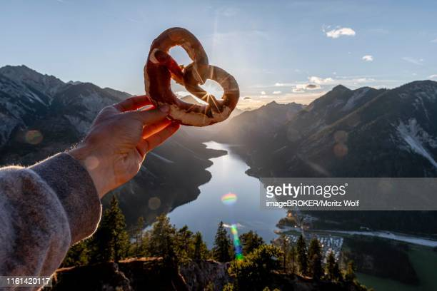hand holding bavarian pretzel in front of alpine panorama, view from schoenjoechl to plansee, tyrol, austria - bavarian alps stock pictures, royalty-free photos & images