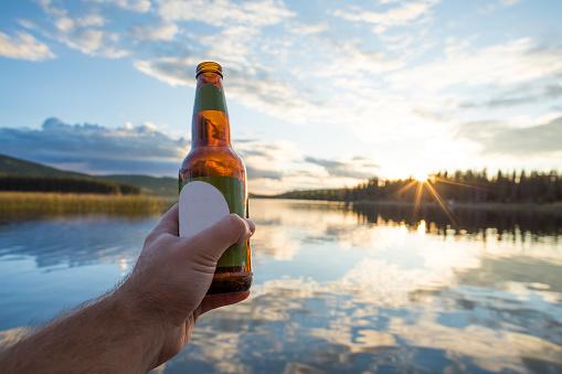 Hand holding beer bottle against lake, Kamloops, British Columbia, Canada - gettyimageskorea