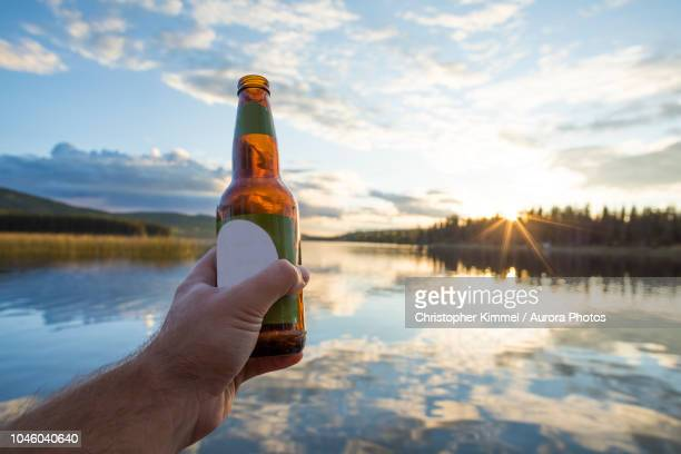 hand holding beer bottle against lake, kamloops, british columbia, canada - beer bottle stock pictures, royalty-free photos & images