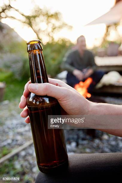 Hand holding beer bottle, close up