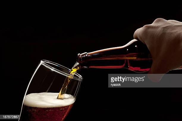 Hand Holding Beer Bottle Pouring Into Glass Isolated Over Black