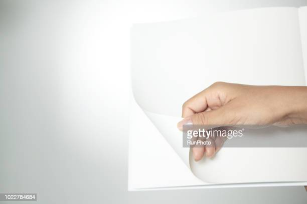 hand holding blank book page - magazine page stock photos and pictures