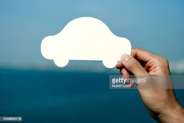 Hand holding blank car shape