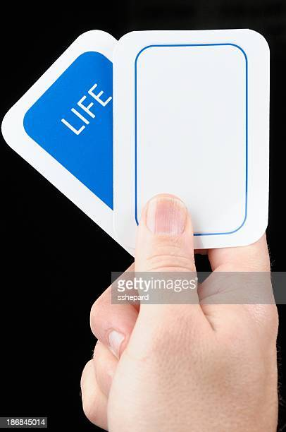 hand holding blank life card - hand of cards stock photos and pictures