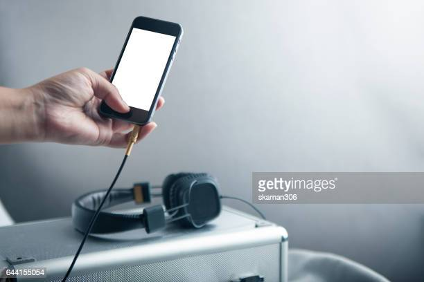 Hand Holding Blank screen Mobile phone connecting vintage headphone on wooden table and darken background