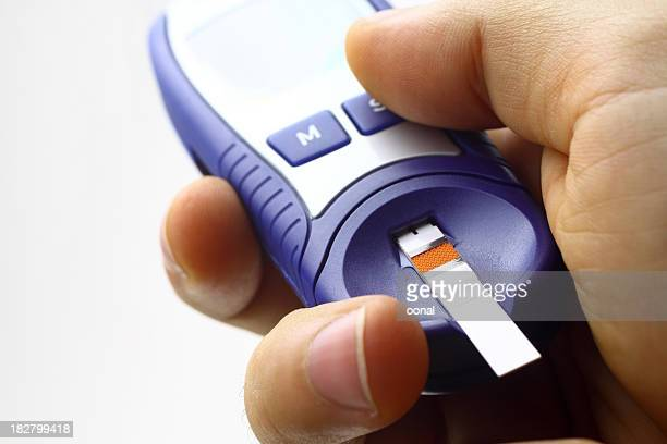 Hand holding blood sugar test device