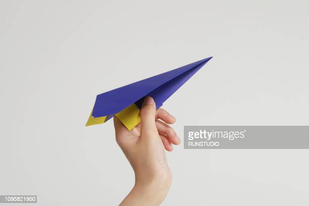 hand holding blue paper airplane - aeroplano di carta foto e immagini stock