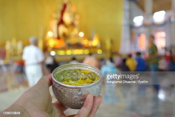 hand holding bowl of scented water to sprinkle water onto a buddha image. songkran festival. - aungsumol stock pictures, royalty-free photos & images