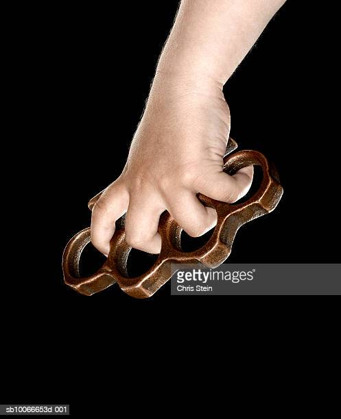 Hand holding brass knuckles on black background