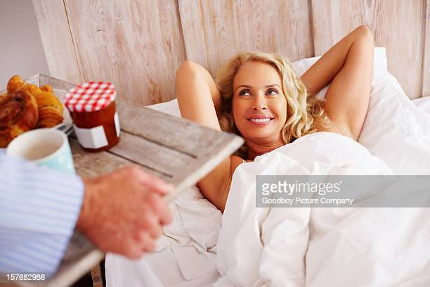 Hand holding breakfast tray to relaxed woman in bed