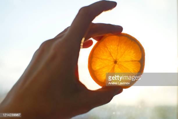 hand holding bright orange against sky and sun. - gesto con la mano foto e immagini stock