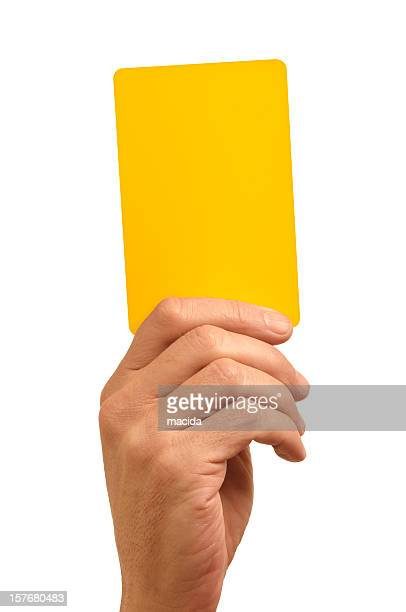 hand holding bright yellow card against white background - yellow card stock pictures, royalty-free photos & images