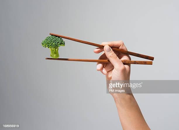 Hand holding broccoli in chop sticks