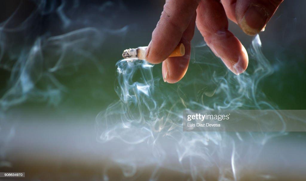Hand holding burning cigarette : Foto stock