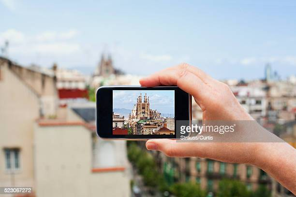 Hand holding camera phone with photo of Barcelona skyline