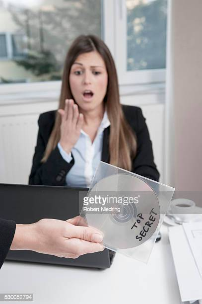 Hand holding CD, young horrified business woman sitting in the background