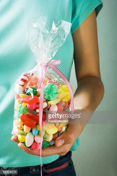 Hand holding cellophane bag of coloured sweets
