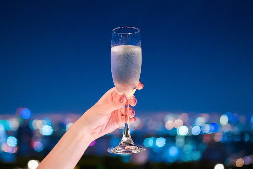 A hand holding champagne glass with beautiful bokeh at night - gettyimageskorea