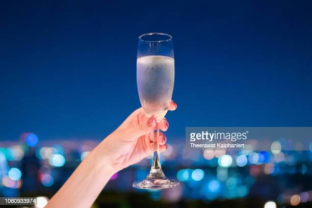 a hand holding champagne glass with beautiful bokeh at night - brindisi bicchieri foto e immagini stock