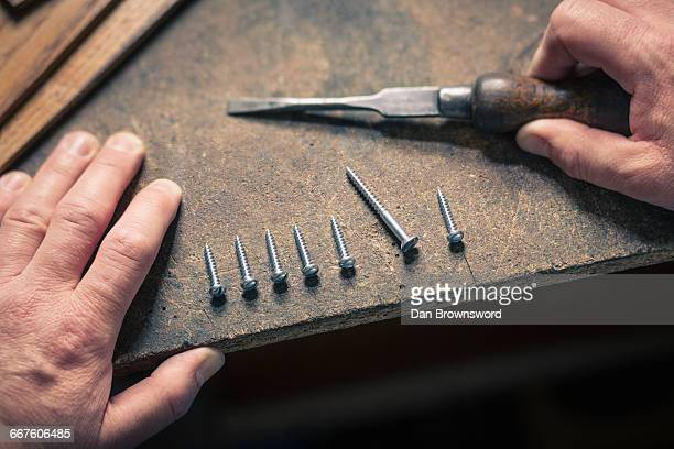 Hand holding chisel, screws in a row