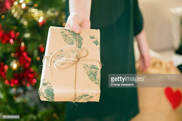 hand holding christmas gift wrapped in brown paper