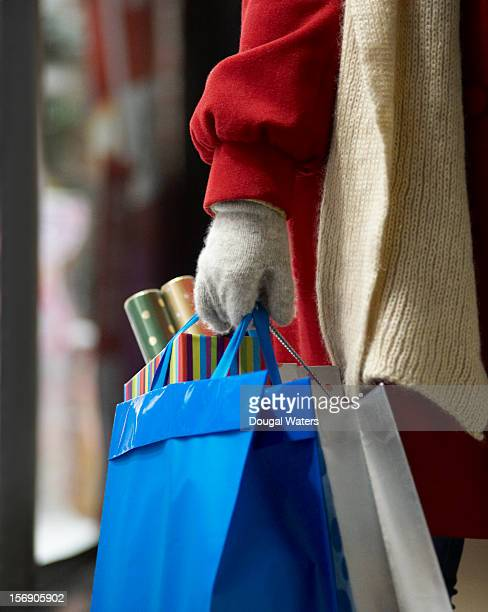 Hand holding Christmas shopping bags.