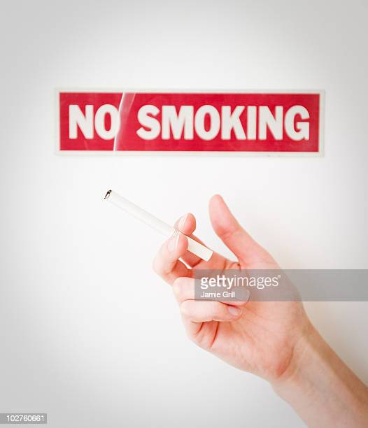 Hand holding cigarette in front of no smoking sign