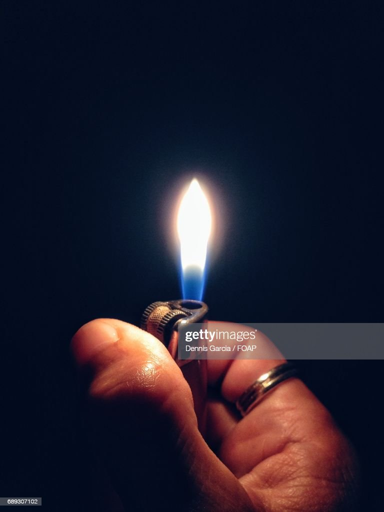 Hand holding cigarette lighter : Stock Photo