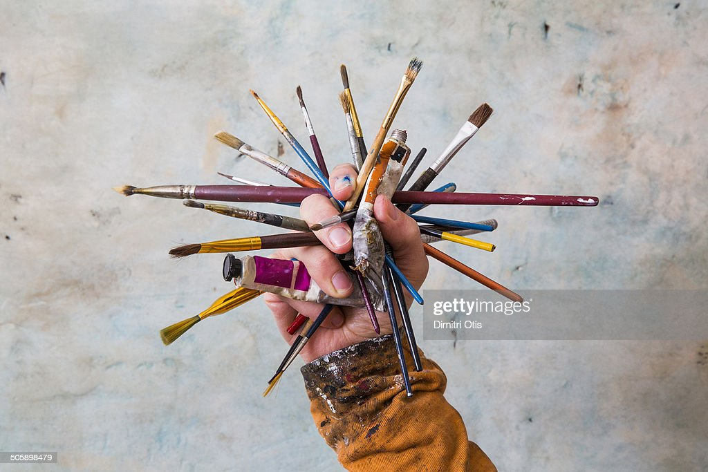 Hand holding cluster of paint brushes and paints : Stock Photo