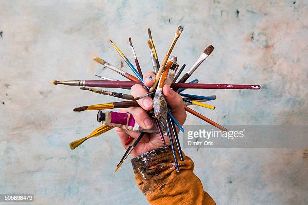 Hand holding cluster of paint brushes and paints